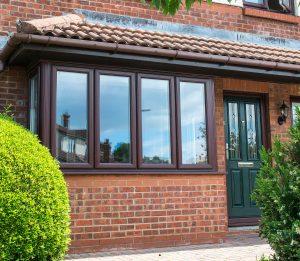 brown upvc bay window with green composite door