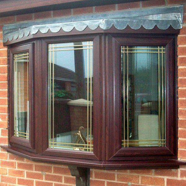 dark wood PVCu bay window with gold lead