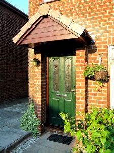 Green composite door with oak upvc door frame and canopy