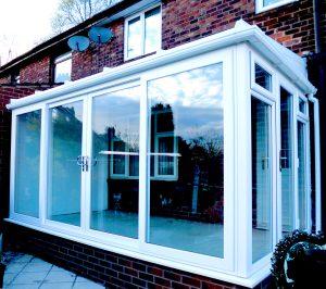 large white conservatory with sliding upvc patio doors