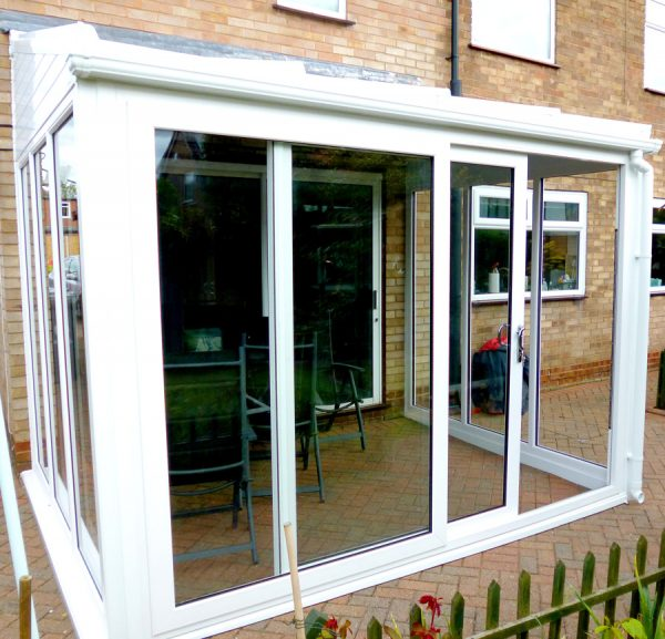 white patio doors opening to a sunroom