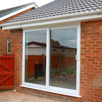 White patio doors on a red brick bungalow home