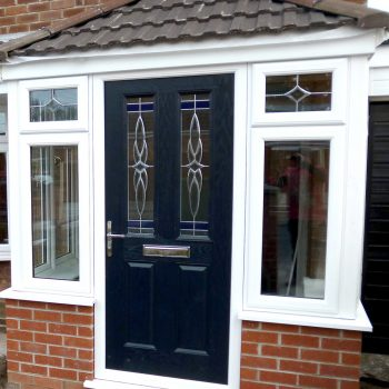white upvc porch with a blue composite door and tiled roof
